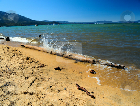 Splashing Water Lake Tahoe stock photo, Summer day on the shore of lake Tahoe on the California side where a small wave crashes against waterlogged log and sends a splash of clear water upward with the sandy beach in the foreground. by Lynn Bendickson