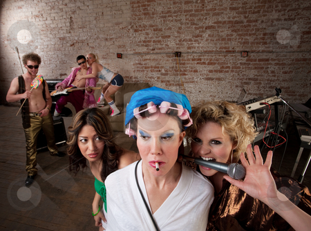 Teasing Neighbors at a Party stock photo, Young lady teasing a woman in curlers with a microphone at a 1970s Disco Music Party by Scott Griessel