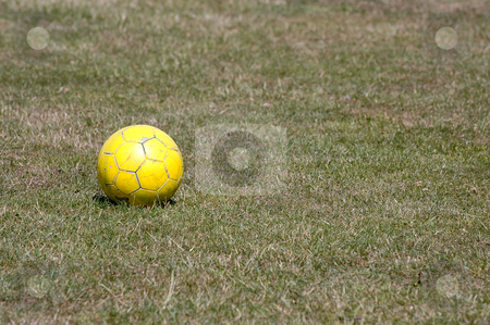 Yellow ball stock photo, Yellow football on green grass. by Lars Christensen