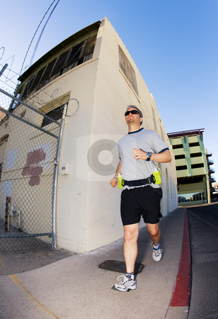 Handsome man runs downtown. stock photo, Man runs in the city for exercise by Scott Griessel