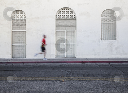 Fast paced man runs down city street. stock photo, Man jogging down city street for exercise by Scott Griessel