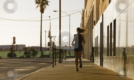Woman out for a morning run stock photo, Woman running down a city block in the morning. by Scott Griessel