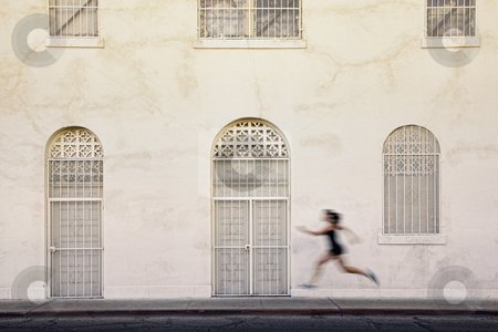 Fast running woman on a city street. stock photo, Woman runs past interesting white and tan building by Scott Griessel