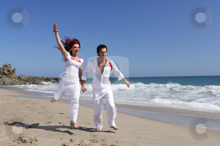 holding hands jumping. Young Couple at the beach jumping for joy holding hands