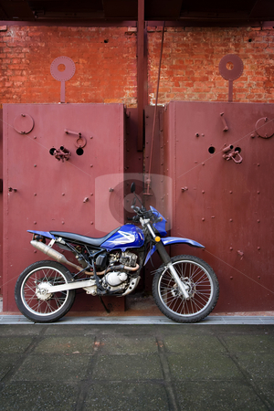 Motorcycle stock photo, Motorcycle leaning on industrial panels in Costa Rica by Scott Griessel
