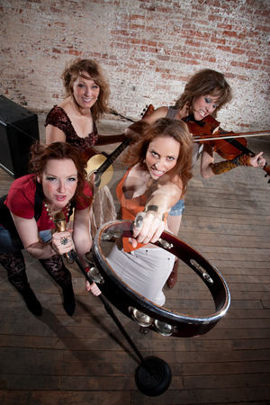 Female musicians stock photo, All-girl band performing in stylish clothing in front of a brick wall by Scott Griessel
