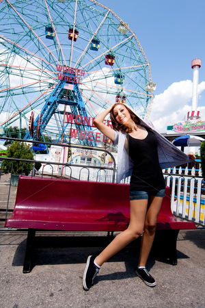 Girl having fun in amusement park stock photo, Beautiful fun happy girl with hoodie shirt at the Wonder Wheel in Coney Island carnival amusement theme park. by Paul Hakimata