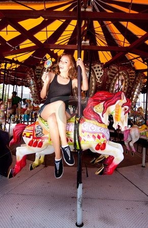 Girl having fun in amusement park stock photo, Beautiful fun happy smiling girl riding horse in carousel merry go round in Coney Island carnival amusement theme park. by Paul Hakimata