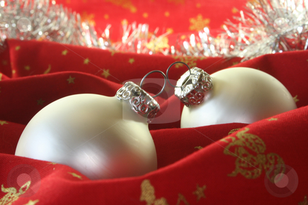 Christmas balls stock photo, Two silver Christmas balls and tinsel chain lie on red fabric by Mar&eacute;n Wischnewski