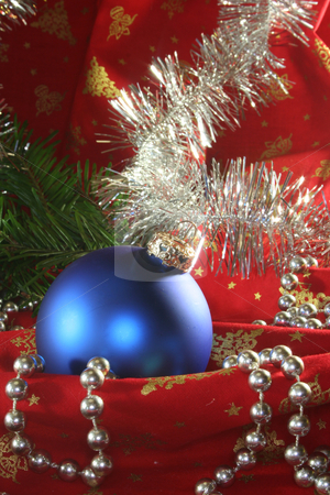 Christmas ball stock photo, A blue Christmas ball and tinsel chain lie on red fabric by Mar&eacute;n Wischnewski