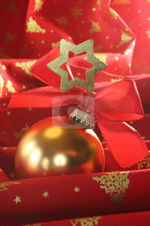 Christmas ball stock photo, A gold Christmas ball with ribbon and star on red fabric by Marén Wischnewski