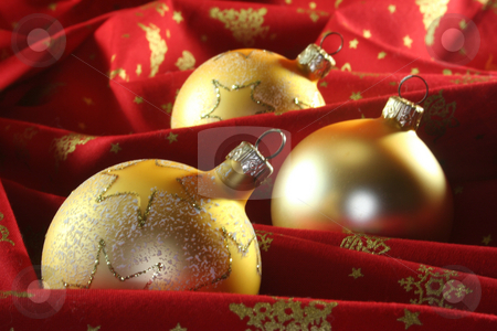 Christmas balls stock photo, Three golden Christmas balls lie on red fabric by Marén Wischnewski