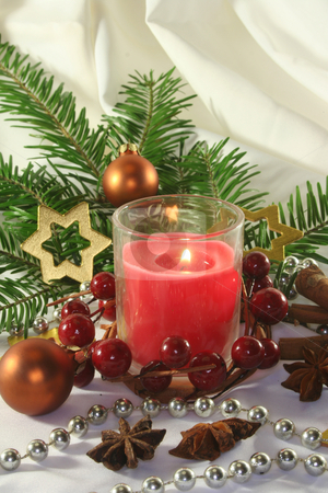 Christmas stock photo, Red candle with Christmas ball, stars and pine branches on a light fabric by Marén Wischnewski