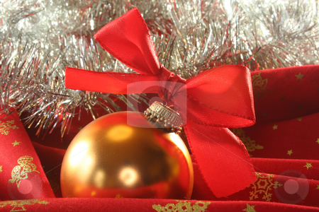 Christmas ball stock photo, A gold Christmas ball with ribbon and silver tinsel chain on red fabric by Marén Wischnewski
