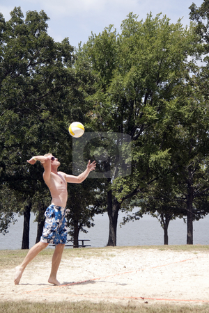 Volleyball stock photo, A man serving a volleyball on a beach court by Kevin Tietz