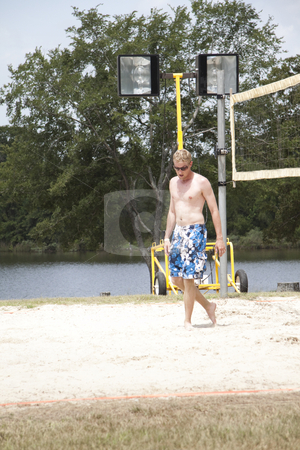 Guy Walking stock photo, A guy walking on a sand volleyball court by Kevin Tietz