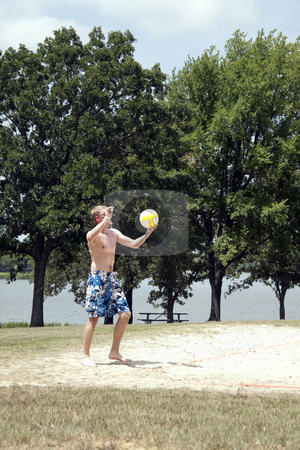 Volleyball Player stock photo, A man serving a volleyball on a beach court by Kevin Tietz