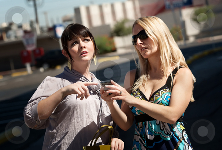 Pretty women lost in the city. stock photo, Two women use cell phone to find the way to go. by Scott Griessel