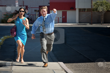 Handsome man and pretty woman are late. stock photo, Man and woman run down street to catch taxi. by Scott Griessel