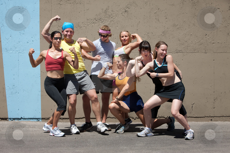 Runners pose for muscle shot stock photo, Group of friends have fun posing after a run. by Scott Griessel