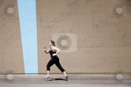 Single woman runs to get in shape stock photo, Woman runs as part of her fitness program. by Scott Griessel