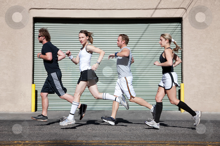 Foursome runs in the city for exercise. stock photo, Beautiful, confident woman runs with friends. by Scott Griessel