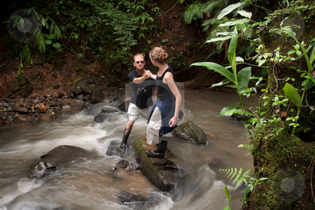 Woman helping man cross Costa Rican river stock photo, Woman helping man cross ruching Costa Rican river by Scott Griessel