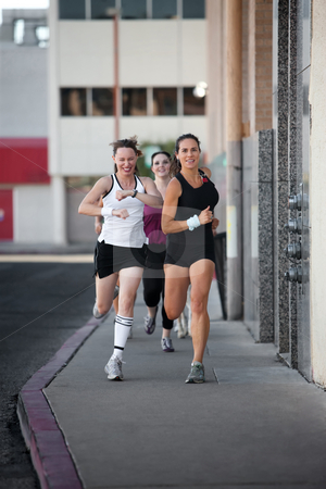 Women racing for fun. stock photo, Group of women racing down a city street for fun. by Scott Griessel
