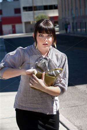 Pretty girl in the city searches purse. stock photo, Young woman frantically searches purse on city block. by Scott Griessel