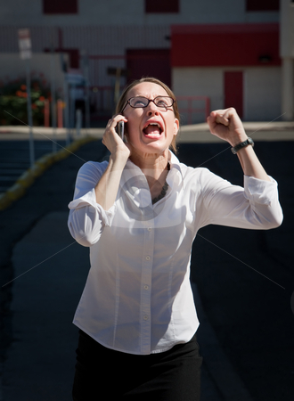 Beautiful woman yells into cell phone stock photo, Terribly upset young woman screams into cell phone by Scott Griessel