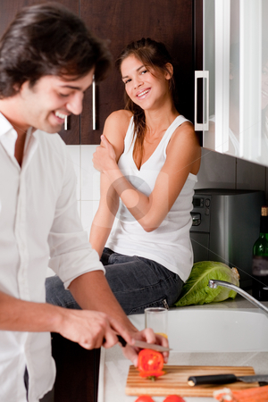 Boyfriend sliceing tomottos with his girlfriend stock photo, Boyfriend sliceing tomottos with his girlfriend in kitchen by Get4net