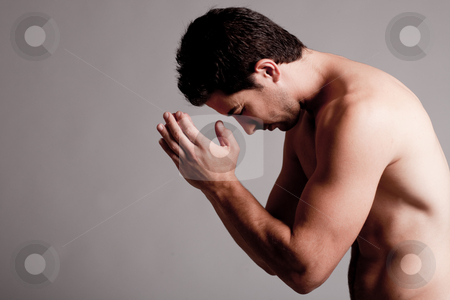 Shirtless man praying stock photo, Shirtless man praying in the grey isolated background by Get4net