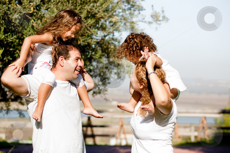 Parents playing with their children stock photo, Children enjoying and playing on their parents shoulders by Get4net