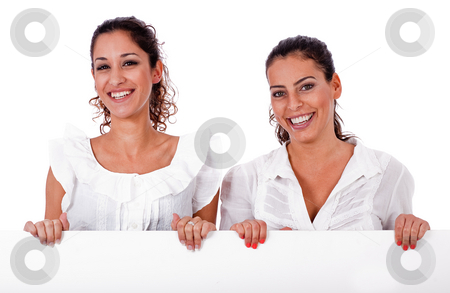 Happy young business colleagues holding a white blank board stock photo, Happy young business colleagues holding a white blank board on white isolated background by Get4net