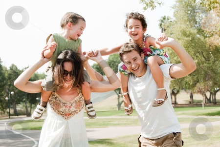 Happy young family stock photo, Young couple embracing and enjoying with two young children by Get4net