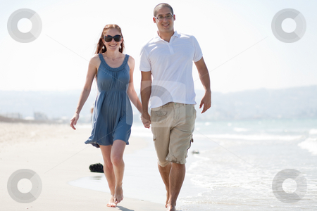 Love couple walk on the beach stock photo, Happy young couple walk at the beach by Get4net