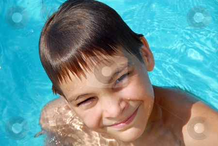 Teen boy in swimming pool portrait stock photo, Happy teen boy in blue swimming pool portrait by Julija Sapic