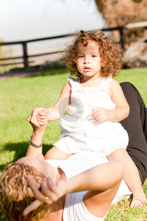 Mom and daughter stock photo, Cute kid with white dress sitting on her mom by Get4net 