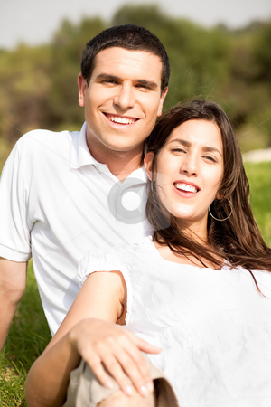 Portrait of Happy young couple sitting and smiling stock photo, Portrait of Happy young couple sitting and smiling in the park by Get4net