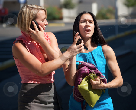 Beautiful women talking on phones in city stock photo, Two women hold multiple conversations on cell phones. by Scott Griessel