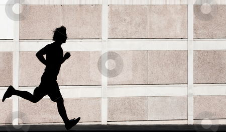 Physically fit man runs for exercise stock photo, Man in the shadows of building runs for exercise. by Scott Griessel