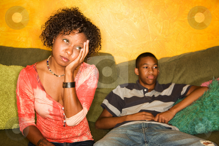 Worried African-American woman sitting with teen stock photo, Worried woman sitting on couch with teen boy by Scott Griessel