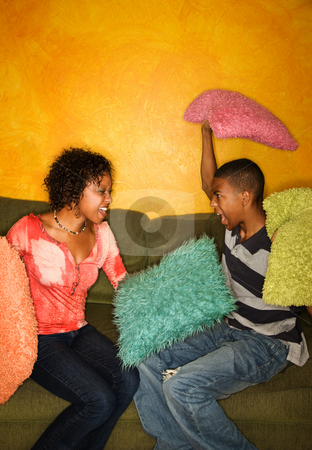 African-Americans having pillow fight stock photo, Woman and teenage boy have pillow fight on green sofa by Scott Griessel