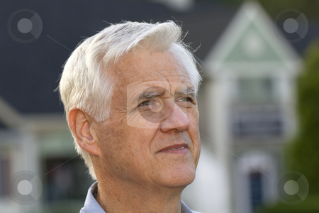 Worried Home Owner stock photo, Portrait shot of senior man with defocused home outlines behind him reflect the universal effect of the recession's housing conditions by Florence McGinn