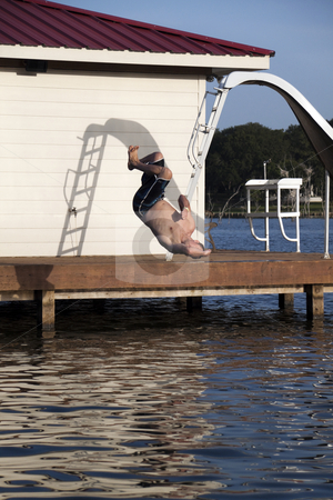 Flip stock photo, A man is doing a back flip off the end of a dock into the water by Kevin Tietz