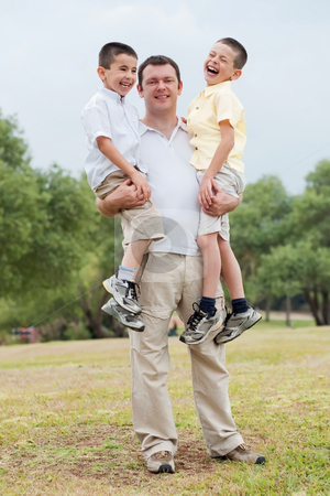 Happy father carrying his two son in his hands stock photo, Happy father carrying his two sons  in his hands on a natural background by Get4net