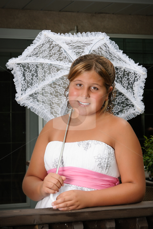 Formal Child Portrait stock photo, A cute young girl, wearing a white dress and holding an umbrella is posing for her portrait by Richard Nelson