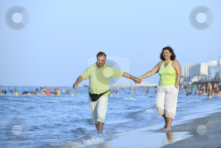Happy seniors couple  on beach stock photo, Happy senior mature elderly people couple have romantic time on beach at sunset by Benis Arapovic