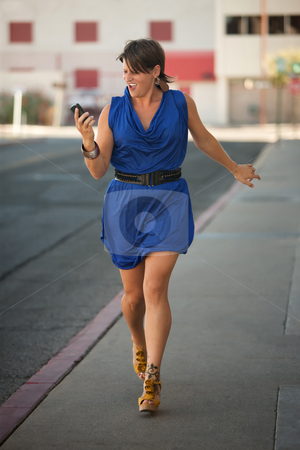Excited woman walks and calls on cell phone. stock photo, Woman walks down the street while making a phone call by Scott Griessel