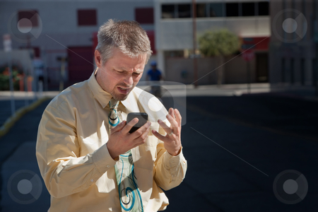 Man is confused by message on cell phone stock photo, Man is frustrated with cell phone coverage. by Scott Griessel